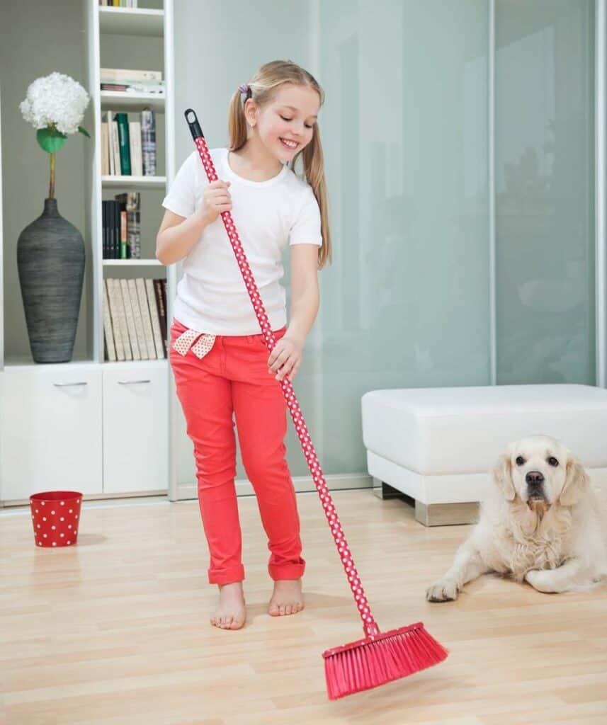 girl sweeping dog hair off floor